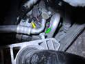 The right side clamp (looking towards the rear of the car) has one bolt (green arrow) that comes in close proximity of an air conditioning line (yellow arrow).