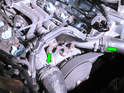 Loosen and slide back the hose clamps on each upper radiator hose (green arrows).