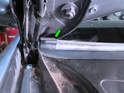 Move the end of the left wiper blade (green arrow) out from behind the hood while laying it back over the windshield.