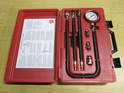 Shown here is a compression tester kit with the pressure gauge and adapter hoses.