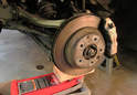 Place a floor jack with a block of wood under the control arm.