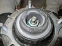 Loosen and remove the 18mm nut holding the retaining collar to the shock absorber.