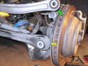 In some cases, you may find that disconnecting the upper control link (green arrow) and lower control link (yellow arrow) from the wheel hub helps to provide enough travel (See our article on replacing rear control arms for more information.