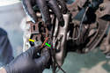 Front Brake Calipers - Pull the brake wear sensor wiring (green arrow) out from under the clip (yellow arrow) on the pad retaining spring.