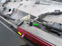 Once the brake light assembly is free, carefully pull the water hose connector (green arrow) up and off the assembly.