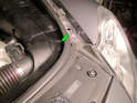 Begin by opening the hood and locating the access panel at the front of the engine compartment near the headlight assembly (green arrow).