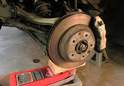 Support the rear suspension using a floor jack placed under the rear control arm as shown here.
