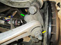 Rear Upper Control Link: Now loosen and remove the 24mm nut (yellow arrow) and bolt (green arrow) holding the link to the wheel carrier.