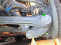 Toe Control Link: Loosen and remove the 24mm nut and bolt (green arrow) holding the link to the wheel carrier.