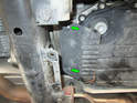 Now loosen and remove the two 10mm bolts (green arrows) holding the heat shield to the transmission.