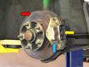 With the wheel off you can see the rotor/disk (red arrow), caliper (blue arrow) and brake pads (yellow arrow).