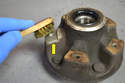 Carefully clean the surface area on the hub where the rotor/disk mounts (yellow arrow).