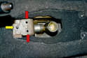 Install the shifter assembly over the tunnel placing the socket bushing into the cup; the shifter will be aligned in the 3rd and 4th gear plane and the two 10mm bolt holes on the bushing bracket should line up with the housing while in this position (red arrows), insert the two 10mm bolts and tighten them down.