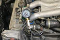 With the threaded end inserted into the spark plug hole, connect the hose to the gauge.