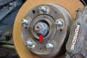 Depending on your vehicle there should be a 32mm or 36mm axle nut holding the axle to the flange (red arrow).