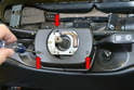 With the steering wheel off use a Philips head screwdriver and remove the three screws on the column surround (red arrows).