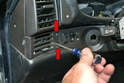 Use a trim removal tool and pop off the trim piece beside the vent and remove the two Philips head screws (red arrows).