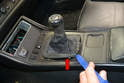 Use a trim removal tool and gently unclip and pull up the shifter knob boot (red arrow).