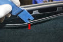 Use a trim removal tool and carefully remove each of the plastic retaining snaps (red arrow) and pull the carpet back.