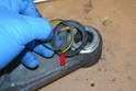 Turn the control arm over and remove the old boot and spring (red arrow).