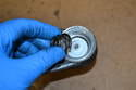 Place the conical tension spring on top of the lower bushing with the wide end down.
