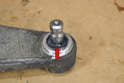 Place grease on the top of the ball joint (red arrow).