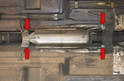 Remove the four 10mm bolts and the heat shield from the center tunnel (red arrows).
