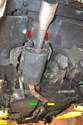 To remove the old muffler you will need to work on three areas: the rear hangers (red arrows), the catalytic convertor flange (yellow arrow) and the middle hanger (green arrow).