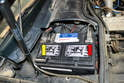 Install the battery in the compartment; connect the positive (+) cable (yellow arrow).