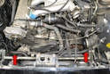 With the air box and intake tubes removed, you can see the metal [pipe that the coolant lines attach too (red arrows).