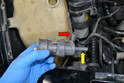 Headlight Pump- Pull the pump up and disconnect the fluid out of the line (red arrow) from the pump.