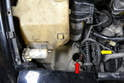Headlight Pump- This photo illustrates the opening in the reservoir that the pump sits in (red arrow).