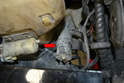 Next, remove the headlight pump (red arrow) from the lower section of the reservoir by pulling it up and out from the grommet it sits in.