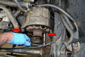Use a 17mm socket and remove the two bolts (red arrows) holding the alternator to the mount.