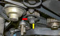 Brace the tensioner with a 24mm wrench (red arrow) and remove the 17mm nut (yellow arrow).