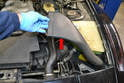 Begin by using a flathead screwdriver and removing the air intake to air box tube (red arrow).