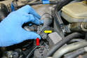 Use a 10mm wrench and remove the two bolts that hold the throttle cable to the intake manifold (red arrows).