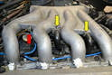Depending on the manifold you have you will have several vacuum lines (red arrow) and hoses attached to it.