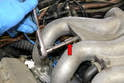 Use a 13mm socket and remove the banjo bolt for the vacuum lines between the three and four intake runners (red arrow).