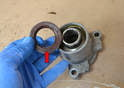 Use a screwdriver or other tool to remove the front gasket/seal (red arrow) from the mount and around the flange.