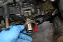 Next, use the pick or a small flathead screwdriver and remove the seal (red arrow).