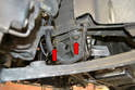 Use a 19mm socket and lower the cross member by loosening but not removing the two bolts on each side (red arrows).
