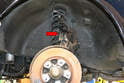 Make sure to hang the caliper safely up out of the way (red arrow).