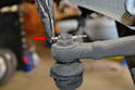 Begin removal by using a set of pliers to straighten out the cotter pin and pull it from the top of the ball joint shaft (red arrow).