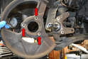 With the rotor off use a 10mm socket and remove the three bolts holding the dust shield in place and remove the dust shield from the spindle (red arrow).