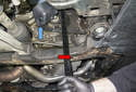 Use a belt tensioner tool with a 3/8-inch drive bit (red arrow) installed.