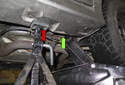 Jacking rear of vehicle: When using a hydraulic floor jack to lift the rear of the vehicle, place the hydraulic floor jack under the rear suspension to body connection (green arrow), raising one side at a time.