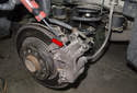 Use a flathead screwdriver and lever the caliper off the rotor (red arrow).