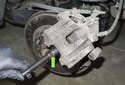 Then press the piston back into the caliper using a brake caliper piston tool (green arrow).