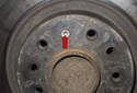 Next, using a T25 Torx bit, remove the brake rotor-mounting fastener (red arrow).